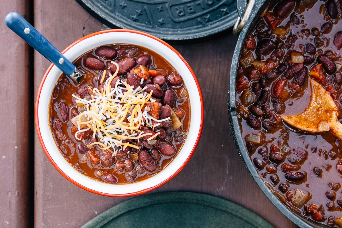 Chili topped with cheese in a red and white bowl