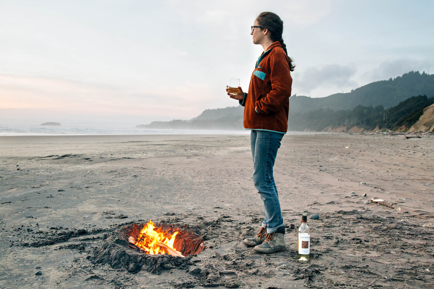Megan standing in front of a bonfire on the beach along the Oregon Coast