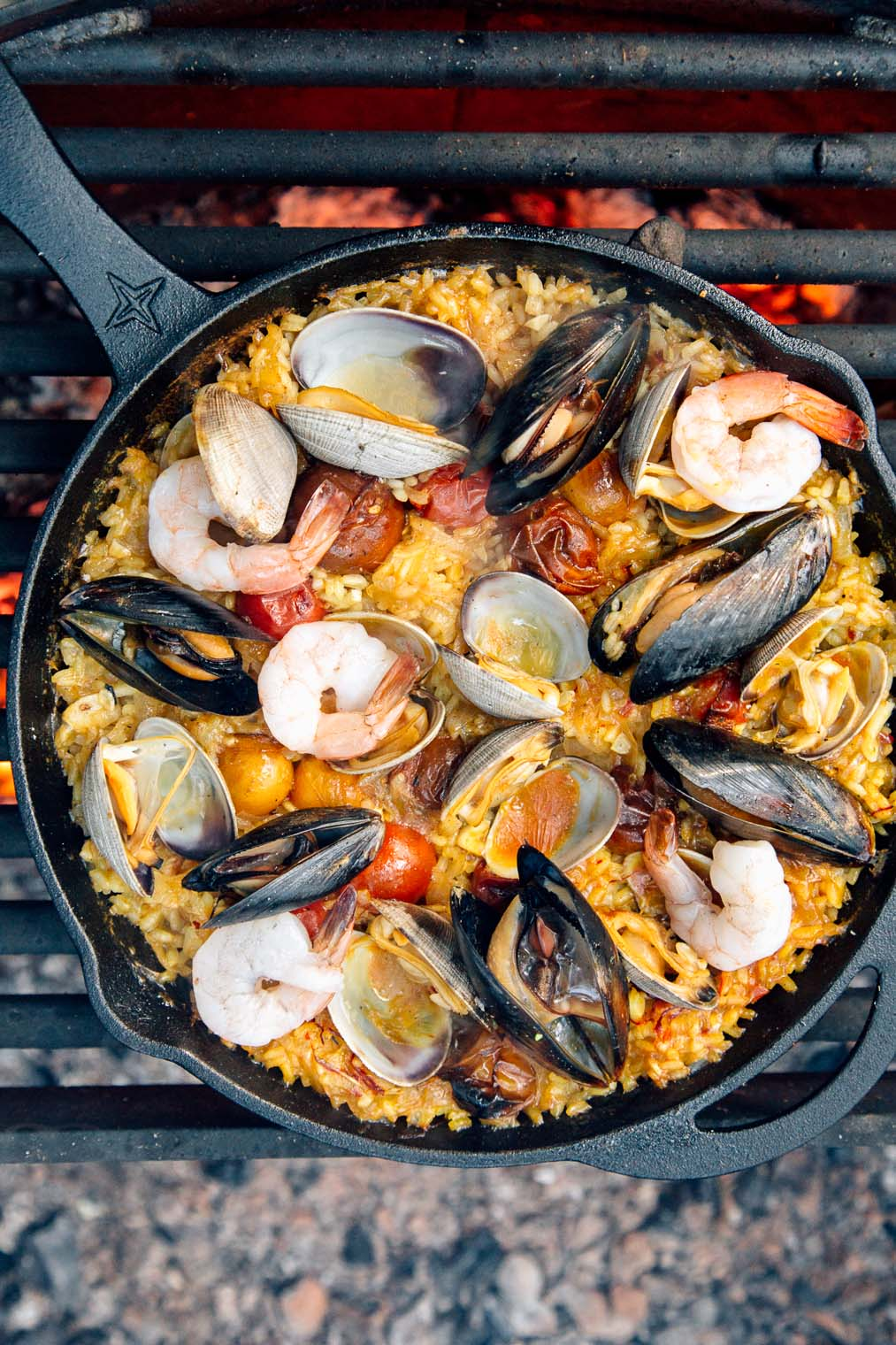 Paella in a cast iron skillet over a campfire