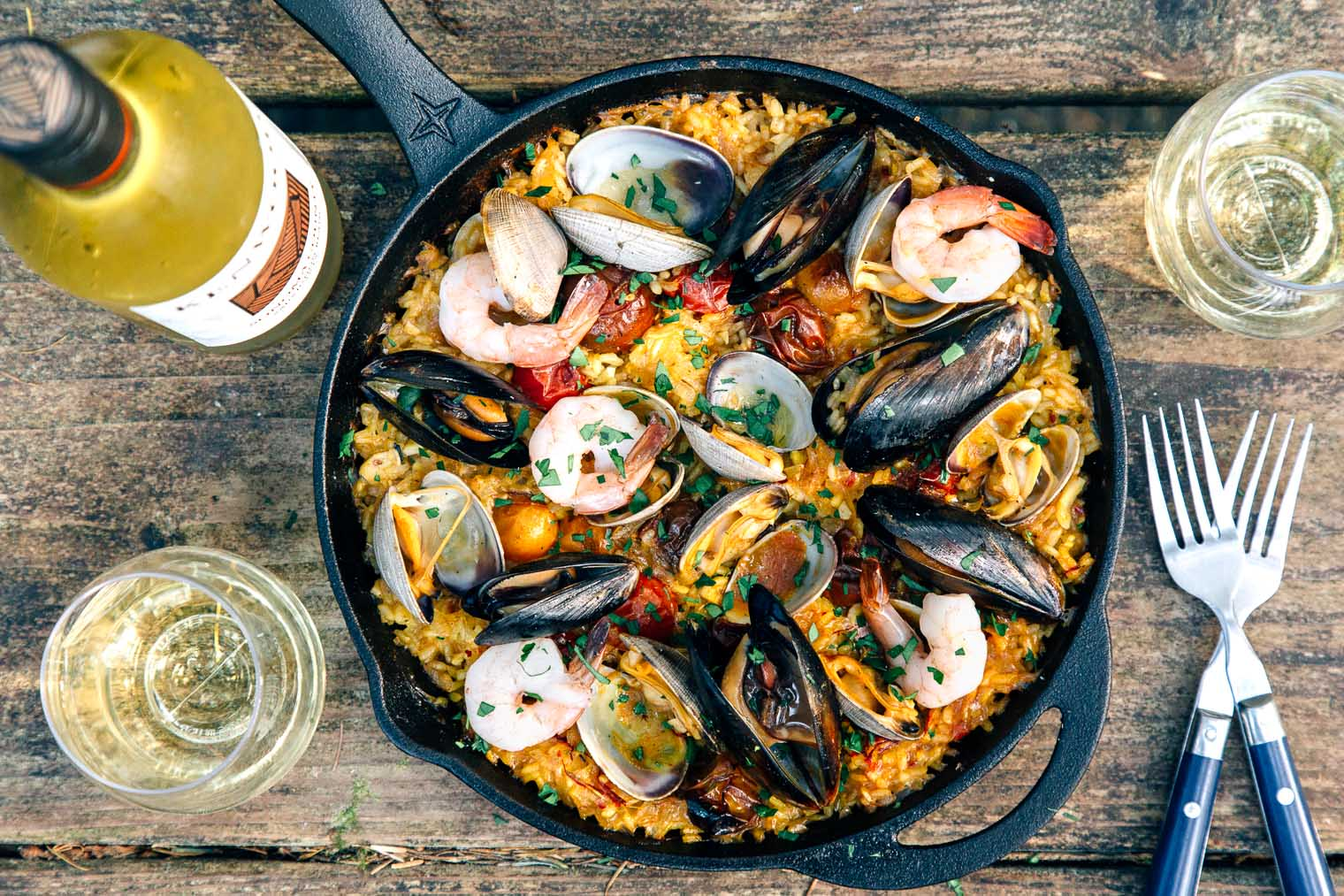 Paella in a skillet on a camping table with forks and a bottle of wine in frame