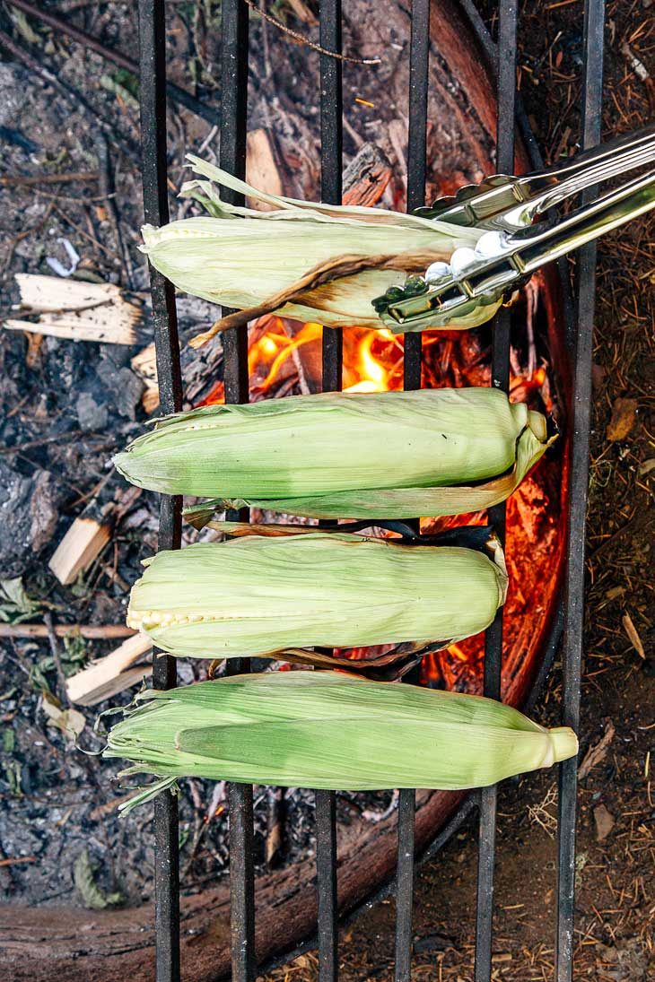Making grilled elotes on the campfire