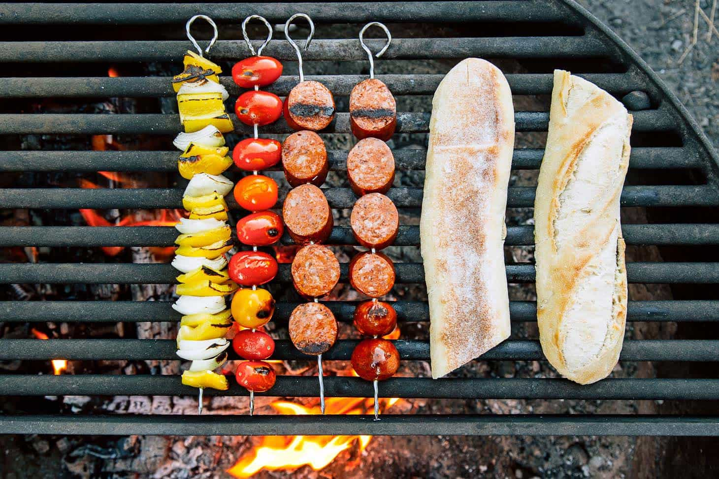 Grilling chorizo kebabs on the campfire